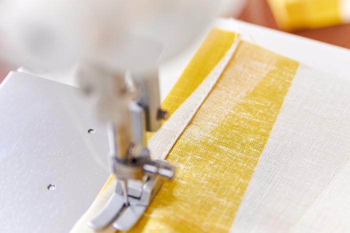 脇を1cm折り、さらに1cm折る三つ折りにし、端を縫います。