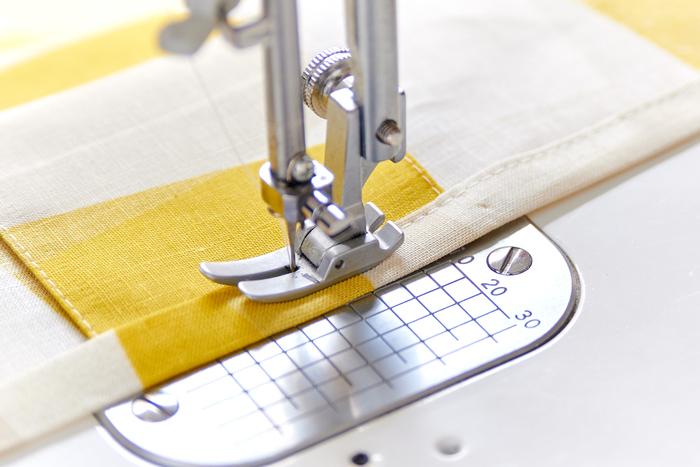 上端を1cm折り、さらに1cm折る三つ折りにします。肩ひもを付け位置に挟み、ミシンで縫います。