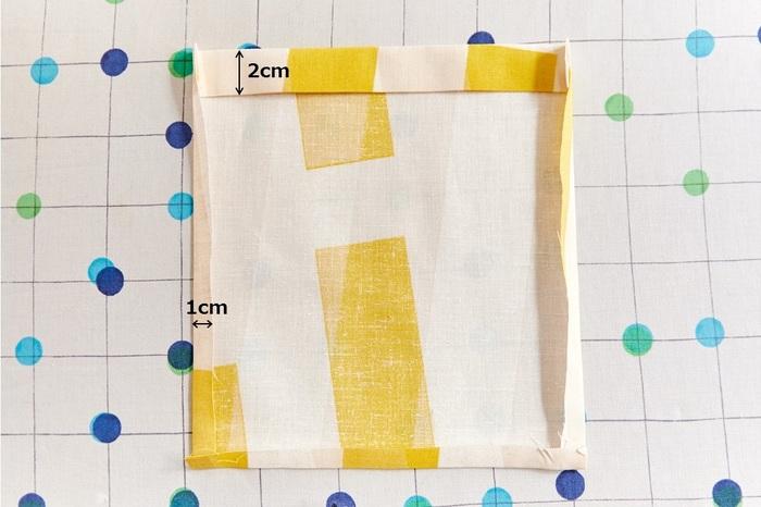 ポケット口を1cm折り、そこから2cm折る三つ折りにします。さらに、周囲を1cmずつ折ります。