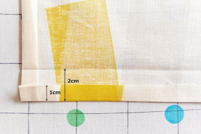 裾を1cm折り、さらに2cm折る三つ折りにします。折った端をミシンで縫います。