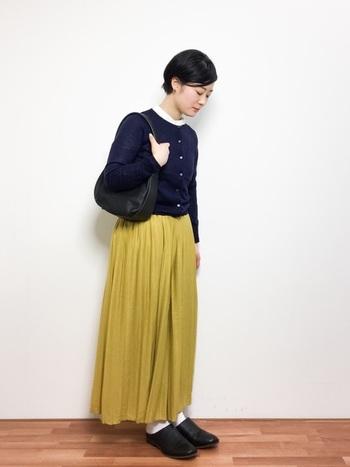 ネイビーのカーディガン×イエローのロングスカートに、黒のサボを合わせたフェミニンコーデ。靴下やインナーで白を取り入れることで、爽やかな印象に仕上がります。