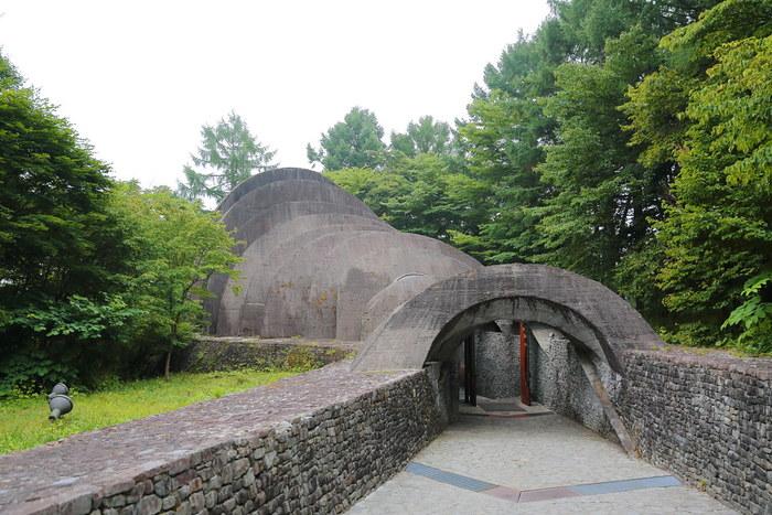 アーチ状の石板が、まるでドミノのように何枚も重なり合い、奥行きを生み出している不思議な光景――こちらの「石の教会・内村鑑三記念堂」は、明治・大正期のキリスト教指導者・内村鑑三氏の功績を讃え、建てられた教会です。  自然との調和を目指す「オーガニック建築」の専門家である、アメリカ人建築家、ケンドリック・ケロッグによる設計です。