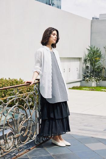 ワイドなシャツとチェックのノースリーブチュニック、ティアードスカートを合わせて異なる丈感で遊んだレイヤードスタイル。色数をしぼって、すっきりとまとめるのがコツ。