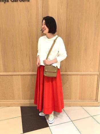 鮮やかな赤色スカートと白いトップスでさわやかな印象に。 スニーカーやカジュアルなカバンとも相性が良いです。