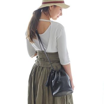 個性的な表情の巾着バッグは、コーディネートの中にちょっとした遊び心を感じさせてくれます。シティーからリゾートまで、幅広いシーンで活躍するアイテムです。