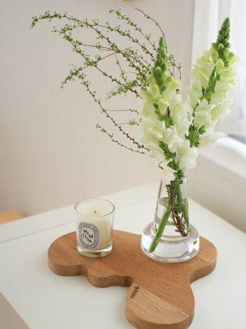 花とキャンドルの色合いを合わせれば、洗練されたインテリアに。木製トレイが温かみを添えています。