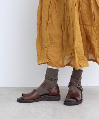 銀杏カラーのスカートに、深いカーキのソックスを合わせて。サンダルをブラウンにすれば「銀杏の木」のような風情もプラスできます。