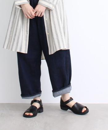 太めのパンツを少しだけロールアップして、ロングシャツと合わせたコーデ。足元はシックな黒のサンダルを合わせて、カジュアルコーデに女性らしさを加えます。