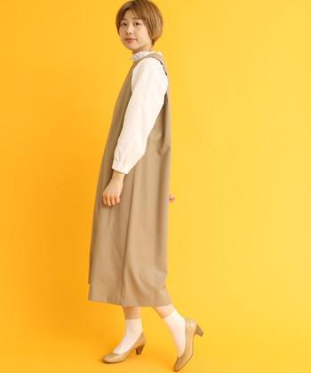 シンプルなジャンパースカートには、白いブラウスを重ねて大人のオンナノコらしさをプラス。その雰囲気を高めるために、ソックス+パンプスでレトロ感を添えましょう。