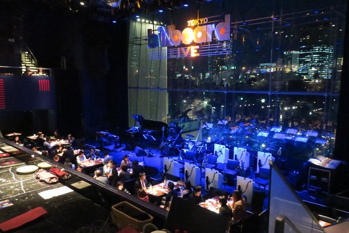 東京ミッドタウン内にある「ビルボード東京」。煌めく都会の夜景をバックにしたステージで、国内外の一流ミュージシャンによる演奏を食事と共に楽しめる空間が特徴。ここに来れば、まさに東京で音楽を聴いているという気分を味わえる雰囲気抜群のお店です。
