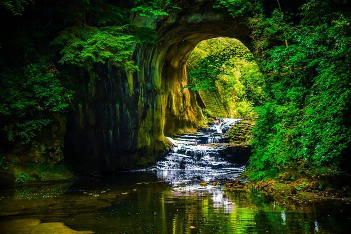 房総半島のほぼ中央に位置する千葉県君津市。SNSで一躍有名になった大人気のスポット「濃溝の滝(のうみぞのたき)」がある清水渓流広場内には、まるでジブリの世界に入り込んだかのような幻想的な光景を見せてくれる「亀岩の洞窟」があります。