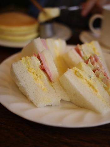Bモーニングはミニサンドイッチ。ふんわりとしたパンに卵やハム、トマト、レタスなど定番の具材が挟まれていて、どこか懐かしいような優しい味わい。 ホットケーキもふわふわの食感が人気で、モーニングではないものの朝から注文する人が多いメニューです。