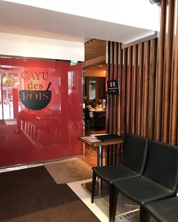 <CAYU des ROIS>は、お粥の専門店。国産米を4時間以上、手間を惜しまず丁寧に煮込んだ、こだわりのお粥を堪能できます。モダンな赤のエントランスが目印です。