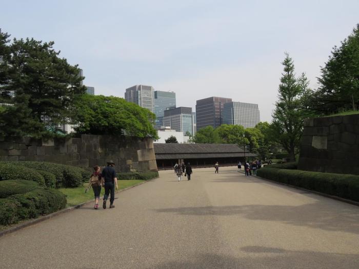 """「三の丸尚蔵館」を過ぎた正面に位置するのが「大手三之門」です。 その手前にあるのが「同心番所」、門を抜けた先にあるのが全長50mを超える「百人番所」です。「百人番所」は、大手三之門を警備する城最大の検問所です。江戸城は度重なる火災に見舞われ、城内建物はほとんど焼失していますが「富士見櫓」・「同心番所」・「百人番所」は、現存の貴重なものです。  """"番所""""とは警備の詰め所のことで、城の奥の番所ほど位の高い役人が詰めていました。「百人番所」には、""""*鉄砲百人組""""と呼ばれた、根来組、伊賀組、甲賀組、廿五騎組の4組が交代で詰め、各組とも与力20人、同心100人が配置され、昼夜を問わず警護にあたり、同心が常に100名詰めていたため、この名前が付いています。   【*家康は、江戸城が万が一落ちた場合の非常時には甲州街道から甲府城へと逃れる構想を立てていたが、その非常時に動員するのが""""鉄砲百人組""""で、それぞれの組屋敷は、全て甲州街道沿い(伊賀組=大久保、甲賀組=青山、根来組=市谷、二十五騎組=内藤新宿)にあった。鉄砲組は、大手三之門の守備が主な職務だったが、将軍が寛永寺、増上寺、日光東照宮へ参詣の際には、護衛も務めた。(画像奥が、現存する建物の一つ「百人番所」)】"""