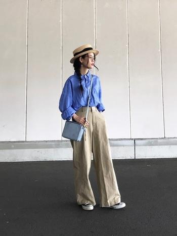 ブラウスの色味を引き継ぐように、バッグも淡いブルーをセレクト。帽子のリボンとスニーカーのブラックがアクセントになっています。