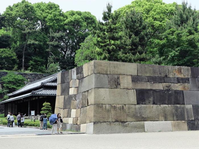 """大手三之門を抜けると左手に「百人番所」がありますが、その右手に「中之門」があります。  門跡ですので、かつての姿を見ることは出来ませんが、威風堂々たる、中之門石垣を間近で眺めることが出来ます。 特に素晴らしいのが隙間なく積まれた巨石。城最大級を誇るこの石は、一つ一つ丁寧に加工され""""切込みはぎ""""という技法によって、隙間なく積み上げられています。石は、瀬戸内海沿岸産の白い花崗岩で、西国の大名から献上されたものであると云われています。  現在、先の「同心番所」「百人番所」を含め、旧江戸城の番所は、三つ残っていますが、大手中之門内側の「大番所」は、残りの一つです。ここ「大番所」は、本丸へ入る前の最後の検問所に当たるため、より厳重であり、他の番所よりも格上の与力や同心によって警備されていました。  【画像の手前が「中の門跡」で、石と石の継ぎ目が横に一直線となるように積む""""布積み""""という石積がなされている。奥の建物が「大番所」。】"""