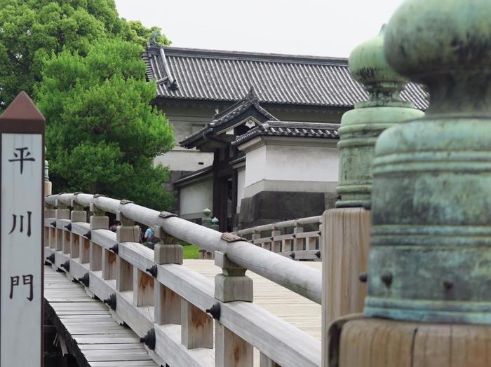 """「東御苑」は、皇居となる以前は、300年もの長きに亘って、徳川幕府の中枢、江戸城があった場所です。豊かな自然環境もさることながら、苑内各所に残る旧江戸城の遺構や、歴史的建造物も見逃せません。  【「皇居東御苑」の出入り門の一つ「平川門」は、旧江戸城・三の丸の正門。本来は、竹橋からの侵入を防御するための橋だが、本丸から最も近い通用門でもあったため、かつては大奥の奥女中らが頻繁に行き来していたため""""お局御門""""とも呼ばれていた。濠を渡る橋で木造であるのは、江戸城でも「平川門」前の「平川橋」のみ。】"""