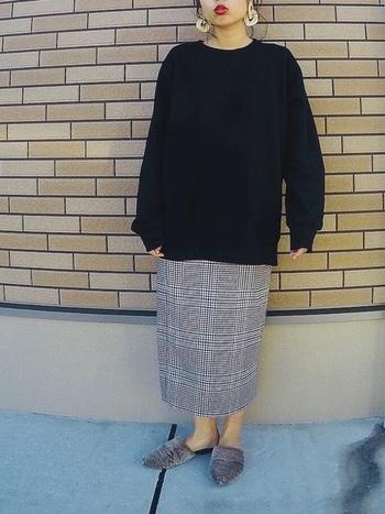 グレンチェックのナロースカートに黒のゆったりニットを合わせたシンプルコーデ。全体をモノトーンでまとめることでチェック柄が引き立ちます。ファー素材のバブーシュサンダルでウォーム感をプラスして。