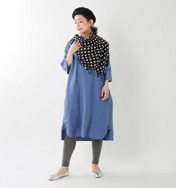 ブルーのワンピースに、濃いグレーのレギンスを合わせたコーディネートです。シンプルなアイテム同士の組み合わせなので、ドット柄のスカーフをゆるく巻いてワンアクセントに。