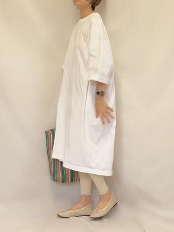 白のオーバーサイズワンピースに、オフホワイトのレギンスを合わせた着こなしです。マルチカラーのトートバッグが、ホワイト系コーデのいい差し色に。レギンスの裾がフリルになっているので、スポーティーなTシャツワンピも女性らしく着こなせます。