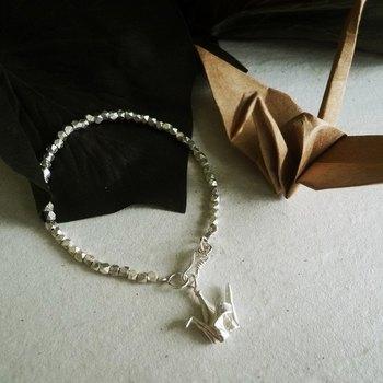 こちらのブレスレットは首に垂れる折り鶴が素敵なデザインです。シンプルながら存在感があって、手首を綺麗に細く見せてくれます。お着物など和装にも似合いそうですね。