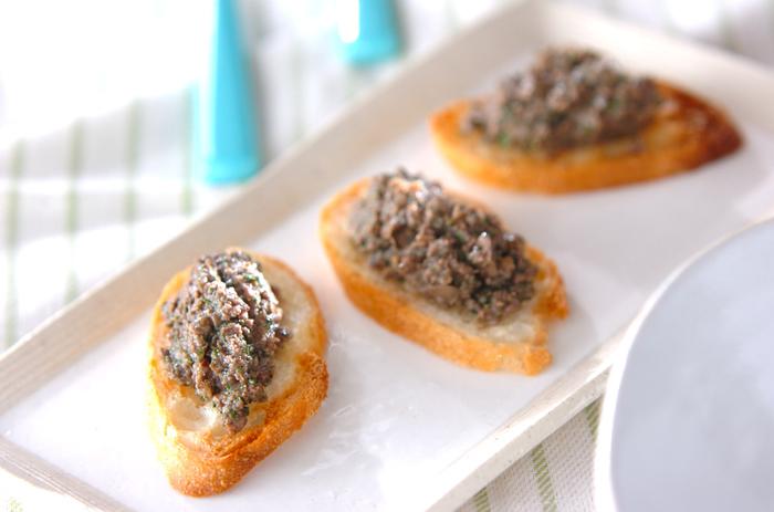 """クロスティーニは""""小さなトースト""""の意味で、おしゃれなアンティパスト。オリーブオイル・チーズ・レバーペーストなど肉の加工品などをのせて食べます。ブルスケッタととても似ていますが、クロスティーニは小さくて薄いトスカーナパンを使うことと、ニンニクをパンにすりこまないことが特徴。アンチョビやケッパーも風味を添えます。"""