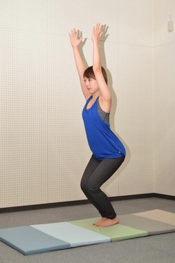 両足を腰幅に開いて立ち、息を吐きながら膝を曲げていきます。次に、息を吸いながら両手を上に。かかとは地を押すように、指先は上へと伸びていくように、背中は丸くならないように意識しましょう。 脚の引き締めと同時に、二の腕のプルプルや肩こりにも有効。