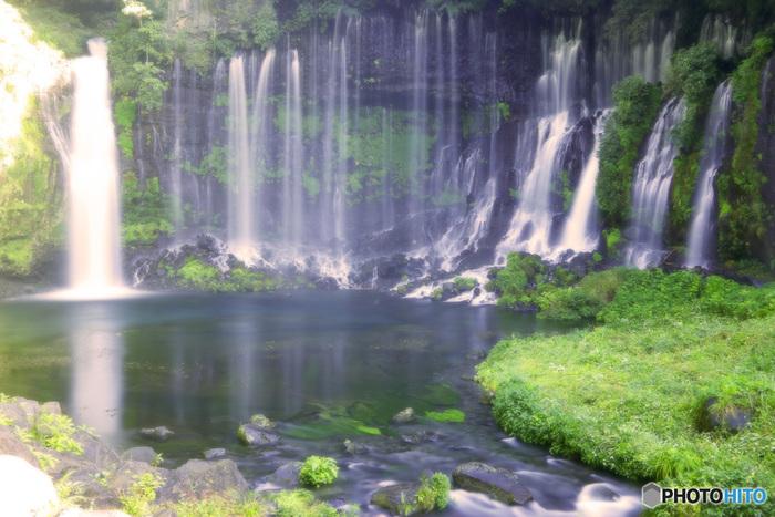 静岡県富士宮市にある「白糸の滝」は、無数の糸を垂らしたような姿がとても美しい滝。 1936(昭和11)年に、国の名勝および天然記念物に指定されています。1950(昭和25)年には、日本観光百選の滝の部で第一位になった滝なんだそうです。高さ20m、幅200~210mから流れ落ちる無数の白い滝は、まるで美しい糸が垂れるように繊細で、滝壺はエメラルドグリーンに透き通り、周りの緑と相まって、大自然の偉大さを感じることが出来ます。