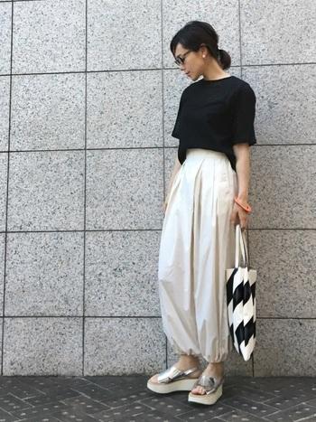 黒の無地Tシャツ×白のバルーンパンツに、厚底のシルバーサンダルを合わせたコーディネート。ボトムスのシルエットや足元、小物の柄でエッジを効かせた、シンプル&クールな着こなしです。