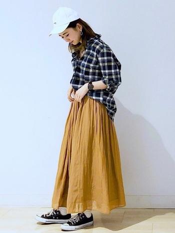 ネイビーのチェックシャツにキレイなマスタードイエローのスカートがよく合っていますね。透け感あるスカートを選んで全体の印象を軽やかにするのがポイント。