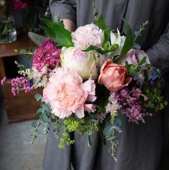 お部屋がパッと明るくなりそうなピンク色の花をたっぷりと束ねたブーケ。可愛らしいフレッシュなピンクにさまざまな質感のグリーンを組み合わせることで、甘さを抑えた大人っぽいブーケに仕上げています。  Mサイズは花瓶に活けやすいボリューム感で、Lサイズは旬の花々をたっぷり使った華やかさ満点の花束です。