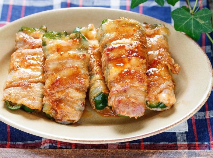 ガッツリ系のおかずが欲しい時は、こちらの豚巻きレシピも必見!半分にカットしたピーマンにキムチとチーズを詰めてから豚バラで巻きます。ピリ辛ダレと相まって、ご飯ともお酒とも相性抜群!10分でサッと作れるので、あと一品にどうぞ。