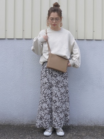 フェミニンな小花柄のスカートには、トップスやバッグなどをスニーカーの色に合わせて着こなすとナチュラルな印象のコーデに。