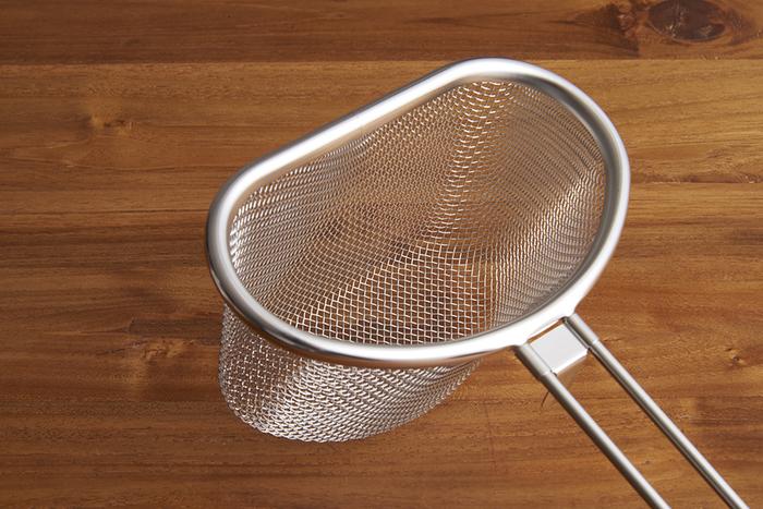 金属加工の産地、新潟県燕三条で、日々の暮らしに役立つ家事道具作りをしている「家事問屋」の茹で分けザル。直径14cm以上の鍋に引っ掛けて使えばひとつの鍋で2種類の食材を同時に茹でられます。ザルの持ち手の根元にはフックがついているので、手を離しても鍋に沈むことがありません。
