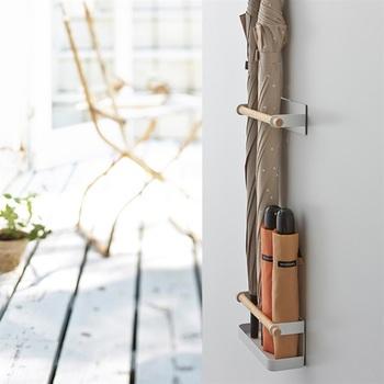 玄関ドアにマグネットでつけるタイプの傘立ては狭い玄関でも使った傘をすっきりと収納することができます。折りたたみも下側に入れておけば、倒れてしまうことがありませんね。