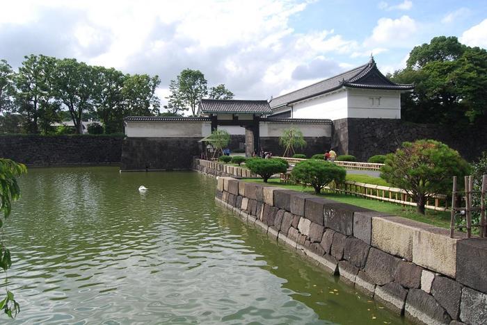 """長禄元(1457)年に、太田道灌によって創築された「江戸城」は、天正18(1590)年に北条氏が滅亡した後、徳川家康の居城と定まりました。以降、家康・秀忠・家光の三代に亘り、西の丸、北の丸の増設、外郭の整備が行われて、江戸城の総講が完成しています。  「東御苑」出入り口の一つ「大手門」は、旧江戸城の正門です。大手町駅が最寄り駅ですが、遠方から上京し、東京観光をしているのなら、JR「東京駅」から歩くのもお勧めです。  【登城する大名らを威圧するような堂々たる「大手門」は、防御力も十分備えた""""枡形虎口*(ますがたこぐち)""""という構造となっている。最初の門を潜ると枡形の空間があり、90度左側にもう一つの門が設けられ、側面の壁には、矢や鉄砲がかけられるように穴が開いている。】"""