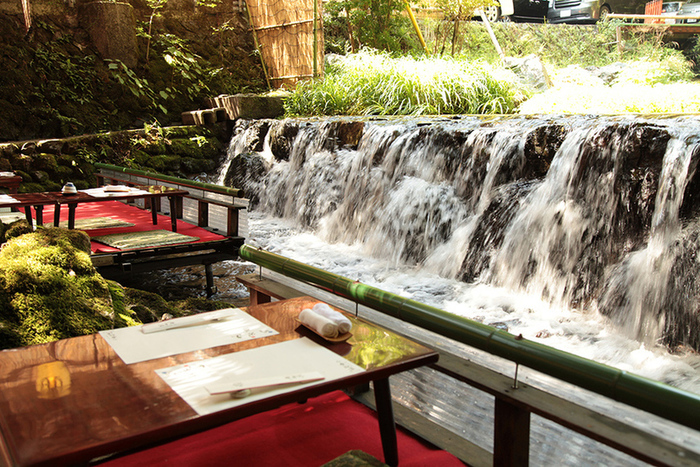 貴船神社 本宮のほど近くに位置する「貴船荘」。手を伸ばせば水面に届きそうな川床は、自然の岩が見事に配された清流を眺めながらゆったりと食事を楽しめる、暑い季節の特等席です。