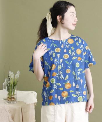作家・イラストレーターの「きたがわじゅり」さんが描いた、お花モチーフのTシャツ。ブルーベースにオレンジとお花のイラストが散りばめられ、爽やかな季節感のある一枚です。