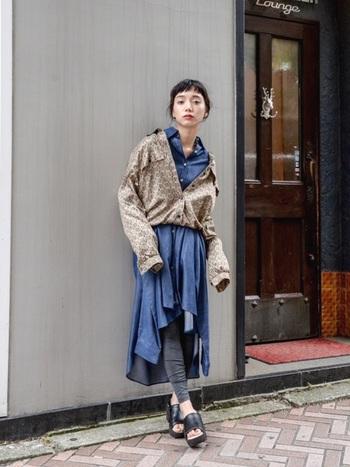 アシンメトリーな裾と4つの袖がついたユニークなデザインワンピースに、シャツをブルゾン風にゆるっと重ね着した個性派レイヤードスタイル。グレーのレギンスや黒の厚底サンダルなど、足元をシックなワントーンでまとめることで、主役のアイテムが引き立ちます。