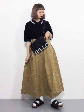 マニッシュな印象の黒のポロシャツには、ベージュのロングスカートを合わせてレディライクに。足元はあえてサンダルを履いて軽快に。