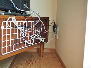 TVボードの裏の配線コードは乱雑になりがち。そんなときも「ワイヤーネット」を使えばスッキリまとめられます。 「ネジフック」を取りつけ、ワイヤーネット」を引っ掛け、コードを「結束バンド」で配線を固定します。