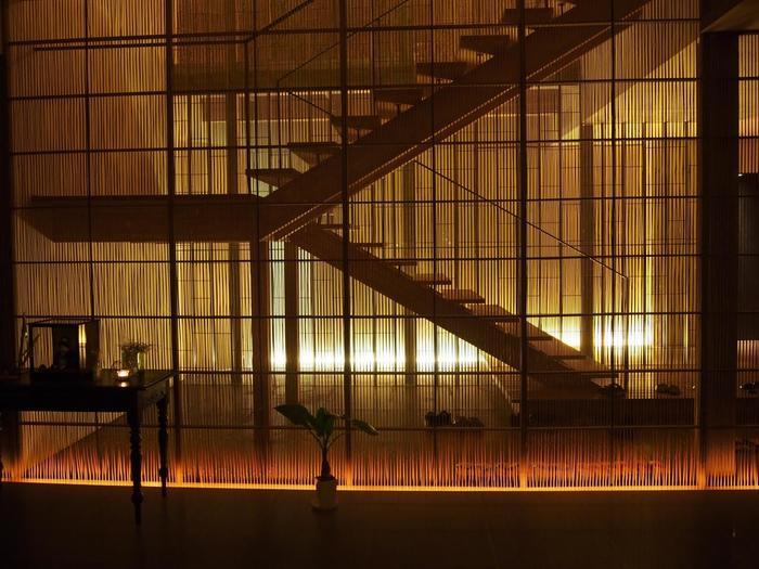 全面にめぐらされた細い縦線は竹のフィルター。さらに淡い緑を帯びたステンドグラス越しに三層の吹抜けが透けて見えます。建築家・隈研吾のデザインによる空間美が感性を呼び覚まします。