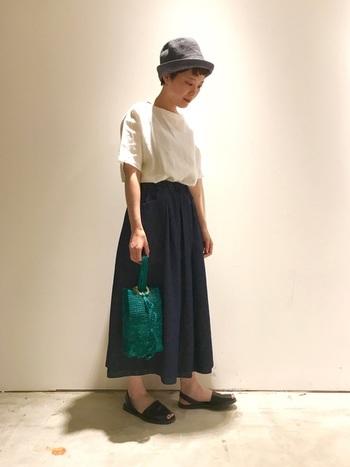 ショートヘアは首元がスッキリしているので、スカートは長めにすると全体のバランスが取れます。 シンプルなスタイルに、緑のバックとおしゃれなハットがアクセントになって洗練されたコーデに。