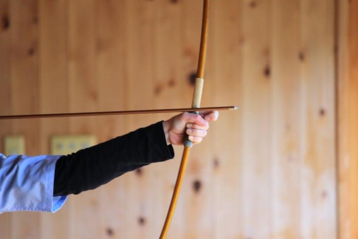 """一点に狙いを定めて矢を放つ""""弓道""""は、集中力が一番の鍵となる日本古来のスポーツ。ほとんど動きのないイメージがありますが、真っ直ぐな姿勢をキープする必要があるため、体幹の強化や猫背の矯正が期待できます。"""