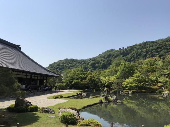 京都の人気エリア嵯峨嵐山に佇む「天龍寺」も古都京都の文化財として世界遺産に登録されており、京都を代表するお寺のひとつ。右手に見える「曹源池庭園」は、日本初の国の史跡・特別名勝に指定された名庭園としても有名です。山々に囲まれ一体化したその景色は圧巻!