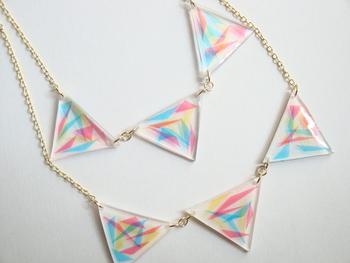 カラフルでシャープな三角がクリアな三角の中に閉じ込められています。とても涼し気で軽やかな印象です。夏の装いにぴったりですね。