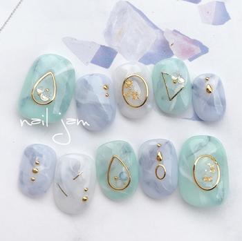 ゴールドの幾何学模様をそれぞれの指に違ったデザインで配して、品のあるネイルに。ブルーとグリーンのスモーキークォーツのようなネイルは夏向きの涼し気な印象です。