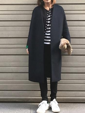シックな黒スキニーは、ロングコートを主役にした大人カジュアルにもぴったりです。ダークトーンに爽やかな白スニーカーとボーダーTシャツをプラスすることで、重くなりがちな冬コーデも軽やかな印象に。