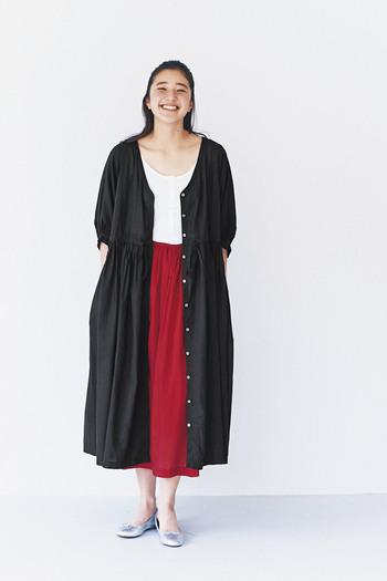白いトップスに赤いスカートのコーデに一枚黒いロングワンピを羽織れば、少し大人な表情を見せることができます。