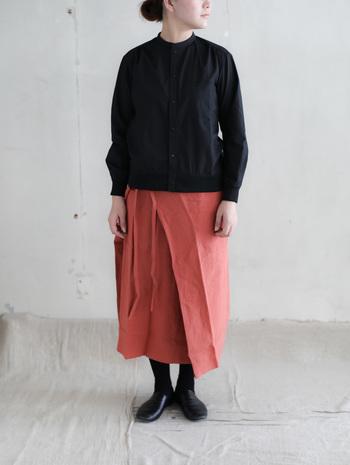 紅葉の秋のようなくすみがかった赤いリネンスカートは、ブラックをまとって冬気分の先取りを。